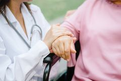 Senior elderly woman`s hand being held by a doctor stock images