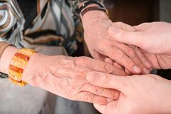 Senior or eldery assistance concept. Young man holds hands of senior woman Stock Photos