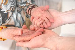 Senior or eldery assistance concept. Young man holds hands of senior woman Stock Images