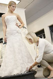 Senior employee adjusting wedding dress of beautiful young bride in bridal store Royalty Free Stock Images