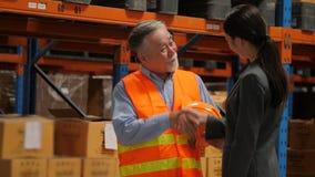 Senior engineer talking with businesswomen and shake hands in warehouse