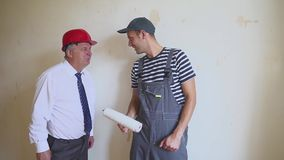 Senior engineer and a young worker having fun and dancing at a construction site. Success in construction stock video