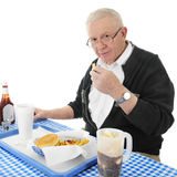 Senior Enjoying Fries. A senior adult man looking up at the viewer as he enjoys a french fry from his fast food basket.  On a white background Royalty Free Stock Photography