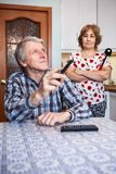 Senior European couple relationship, man watching tv with remote control while his angry wife standing behind in kitchen. Senior European couple relationships Stock Images