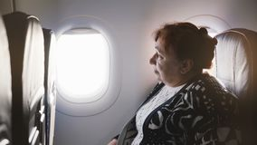 Senior European female airplane passenger sitting on the airplane window seat, nervous and scared to fly, looking around stock video