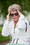Senior European woman with tension headache sitting on a bench after jogging in park Royalty Free Stock Photography