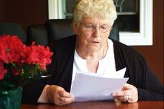 Senior executive. Senior woman working hard , doing paperwork stock image