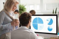 Senior executive checking annual report on computer screen helpi. Statistics data team analysis concept, senior serious executive checking annual financial Stock Photography