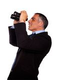 Senior executive looking up through binocular Stock Photography