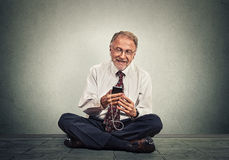 Free Senior Executive Man Sitting On A Floor Using Smart Phone Texting Listening Music Royalty Free Stock Photography - 63247717