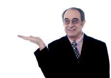 Senior executive posing with an open palm Stock Photo