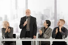 Senior executive speaking, colleagues clapping Royalty Free Stock Images