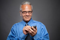 Senior Executive texting looking at camera Stock Photos