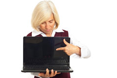 Senior executive woman pointing to laptop. Screen and looking down isolated on white background Royalty Free Stock Photo