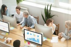 Senior executives teaching young employees in office, mentoring. Senior executives teaching young employees in office, diverse corporate workers staff group royalty free stock photos