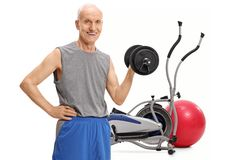 Senior exercising with a dumbbell in front of a cross training m. Achine and a pilates ball isolated on white background stock photos