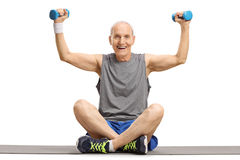 Senior exercising with small dumbbells on an exercise mat. Isolated on white background Stock Images