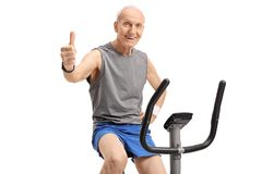 Senior exercising on a stationary bike and making a thumb up sig. N isolated on white background Stock Photos