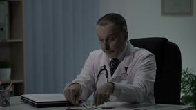 Senior experienced physician exhausted after day shift at hospital, overworking. Stock footage stock video footage