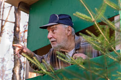 Senior with expressive face. Elderly man with an astonish expression looking through his homemade hunting shack in Quebec forest Canada Stock Image