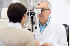 Senior eye specialist look in ophthalmoscope and perform eye rev Stock Photography
