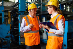 Senior Factory Manager. Portrait of senior factory manager talking to young assistant writing down instructions, both wearing hardhats and reflective jackets stock image