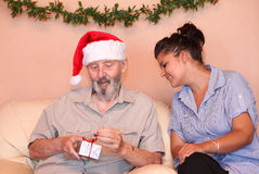 Senior family christmas. Christmas holidays eldely man with carer or nurse opening present or gift Royalty Free Stock Photo