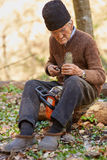 Senior farmer servicing his chainsaw after use Royalty Free Stock Photo