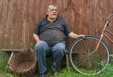 Senior farmer sitting on a bench Royalty Free Stock Image