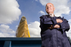 Senior farmer standing with crops filling bin behind him Royalty Free Stock Photo
