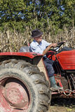 Senior farmer using an old tractor to plow his land Stock Photos