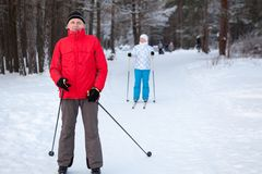 Senior father with adult daughter skiing on cross-country skis in winter forest Stock Images
