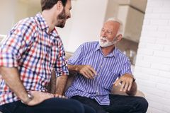 Senior Father With Adult Son Relaxing On Sofa. At Home stock photos