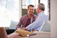 Senior Father With Adult Son Relaxing On Sofa At Home Royalty Free Stock Photo