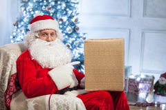 Senior Father Christmas is ready for greeting. Old Santa Claus is sitting in a chair and smiling. He is holding a box of gif and pointing his finger at it with Stock Photography