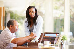 Senior Father Discussing Document With Adult Daughter Stock Image