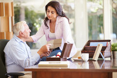 Senior Father Discussing Document With Adult Daughter Stock Images