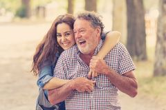 Happy daughter embracing her senior father from back in the park stock photos