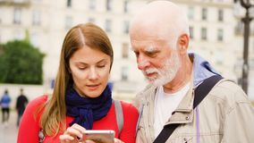 Senior father and his young daughter standing on street using smartphone. Happy family together stock footage