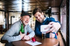 Senior father and his young son with smartphone in a pub. stock images