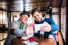 Senior father and his young son with smartphone in a pub. royalty free stock photo