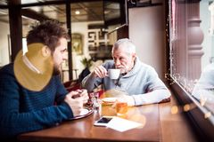 Senior father and his young son in a cafe. Senior father and his young son drinking coffee in a cafe Royalty Free Stock Images