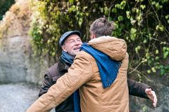 Senior father and his young son on a walk, hugging. Senior father and his young son on a walk in town, hugging stock photos