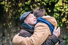 Senior father and his young son on a walk, hugging. royalty free stock photos