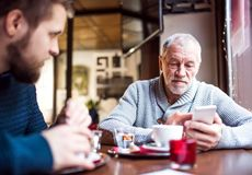 Senior father with smartphone and young son in a cafe. Senior father with smartphone and his young son in a cafe. Old men making text messaging Stock Photos