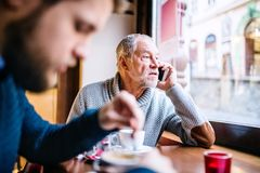 Senior father with smartphone and young son in a cafe. Senior father with smartphone and his young son in a cafe. Old men making a phone call Stock Images