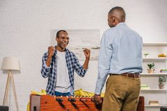 Senior father and smiling adult son playing table football. At home stock photo