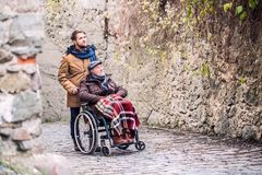 Senior father in wheelchair and son on a walk in old town. Royalty Free Stock Photos