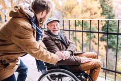 Senior father in wheelchair and young son on a walk. Father in wheelchair and young son on a walk. A carer assisting disabled senior man Royalty Free Stock Image