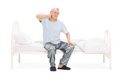 Senior feeling pain in the neck seated on a bed Royalty Free Stock Image